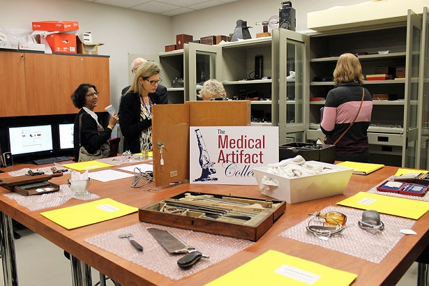 The interior of the medical artifact collection with people looking at items spread carefully across a few tables.